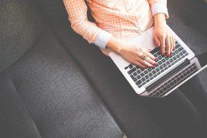 Dziewczyna z komputerem na kolanach