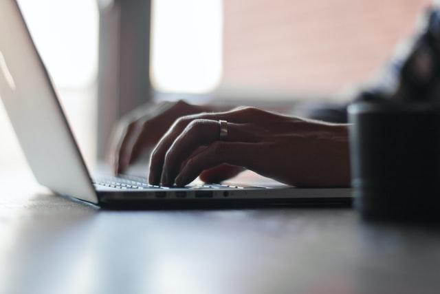 Człowiek siedzący przy laptopie