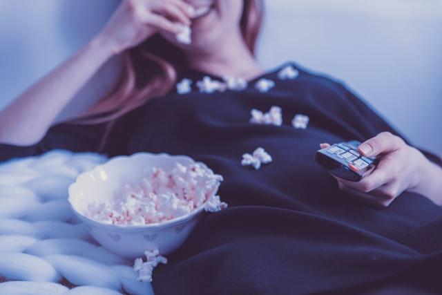 kobieta oglądająca film i jedząca popcorn